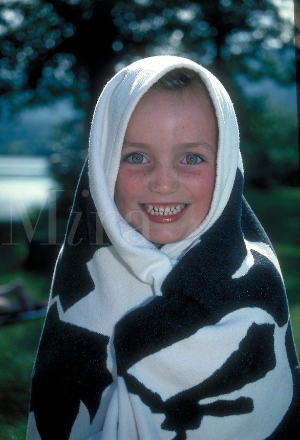 Smiling young girl wrapped in a black and white patterned towel. Leoni. Germany.