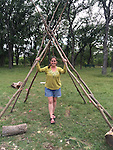 Heather Kuhlken under one of the teepees built with reclaimed Crepe Myrtle and lashing knots.