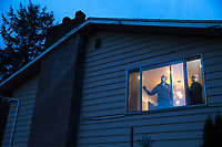 Pat and Bob McCauley, self-quarantined at their home in Kirkland, Wash. can see the red flashing lights of the medics that come and go from the Life Care Center from their window on March 10, 2020. Their good friend, a Life Care resident, died on Sunday of COVID-19. They are mourning him, and anxiously waiting for the results of their COVID-19 tests. They must wear masks when they around each other. Otherwise they need to stay in separate bedrooms and bathrooms in the house. (photo by Karen Ducey for the LA Times)