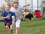 Brayden and Ethan Jacobs play during their brother Justin's football practice in Ankeny.  Heather, seated at rear, lost her husband, Eric, in a plane crash in 2006 when she was eight months pregnant with their youngest, Ella, and has since been raising her five young children on her own.
