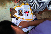 """A Mayan man cleans dried-up bones of a un unborn baby from his family during the bone cleansing ritual at the cemetery in Pomuch, Mexico, 29 October 2019. Every year on the Day of the Dead, people of Pomuch, a small Mayan community in the south of Mexico, visit the cemetery to take part in a pre-Hispanic tradition of cleaning of bones of their departed relatives (""""Limpia de huesos""""). People who die in Pomuch are firstly buried for three years in an above-ground tomb then the dried-up bodies are taken out, bones are separated, wrapped in a decorated cloth, put into a wooden crate, and placed on display among flowers for veneration."""