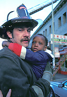 fireman rescuing scared African American toddler