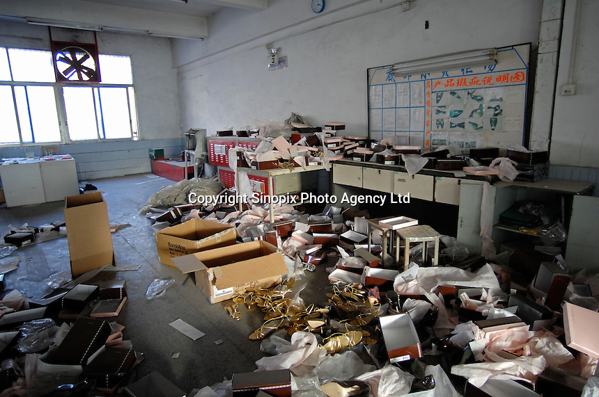"""The ransacked store-room of the  Dingfu Factory in Houjie Town, Dongguan, China. A sign outside the factory that made shoes for Zara and Nine West amongst others, reads that the """"Dongguan People's Court have closed the factory"""". As the economy changes and Chinese labour gets more expensive, factories are closing leaving ghost towns behind them..20 Dec 2007"""