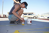 Mission Bay High School, San Diego CA, USA.  Saturday, October 10th 2015:  Local artist Lorrie Blackard Friet works with Mission Bay High School students and community members paint a street mural in front of the High School Gym.  The mural installation was funded by the non-profit organization Beautiful PB through a grant from SANDAG.