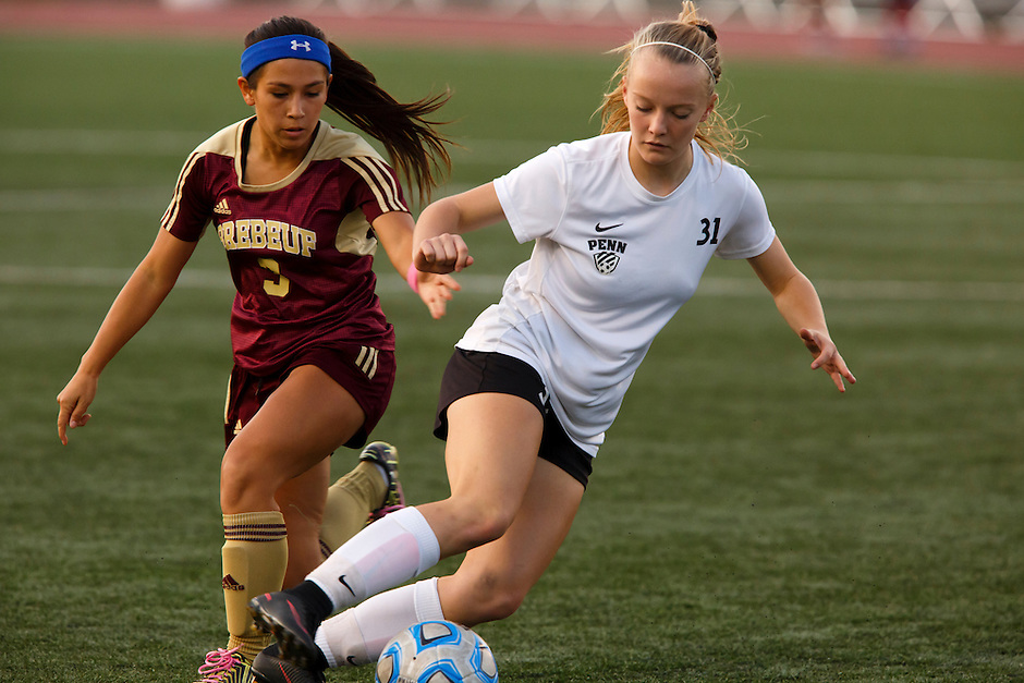 Penn's Lauren Hamilton (31) plays the ball in front of Brebeuf Jesuit's Alexa Holl (3) during the IHSAA Class 2A Girls Soccer State Championship Game on Saturday, Oct. 29, 2016, at Carroll Stadium in Indianapolis. Special to the Tribune/JAMES BROSHER