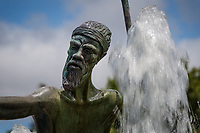 Close-up of an Australian Aboriginal, creased and bearded - one detail of a statue in a water fountain outside a medical office building in Fremont, California.