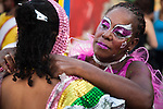 A woman applies makeup to a young girl for the parade of Llamadas during Carnaval in Montevideo, Uruguay.