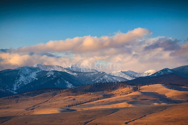 The golden hues of sunlight on the foothills  at the northern edge of Missoula Valley in western Montana