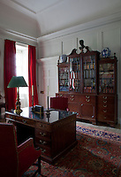 An impressive antique, glass paned book case stands aganist one wall in Lord Dumfries's study