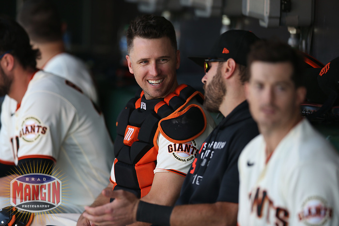 SAN FRANCISCO, CA - AUGUST 1:  Buster Posey #28 of the San Francisco Giants smiles in the dugout during the game against the Houston Astros at Oracle Park on Sunday, August 1, 2021 in San Francisco, California. (Photo by Brad Mangin)