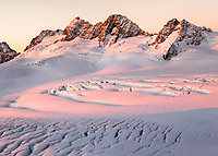 Pastel colours of sunset over mountain ranges of Southern Alps with Explorer Glacier crevasses in upper parts of Fox Glacier NEVE, Westland Tai Poutini National Park, West Coast, UNESCO World Heritage Area, New Zealand, NZ