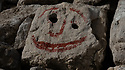 A rock with a face painted on it, in red, on the Praia do Ouro, Sesimbra, Portugal.