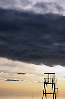 Storm clouds gathering over a lifeguard tower at sunset, Marseille, France.
