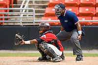 Catcher Leonel De Los Santos #2 of the Hickory Crawdads and home plate umpire Doug Vines at L.P. Frans Stadium June 21, 2009 in Hickory, North Carolina. (Photo by Brian Westerholt / Four Seam Images)