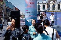 China. Shanghai. Downtown. City center. A woman tries a red lipstick at a make-up stand in front of a big shopping center.  © 2002 Didier Ruef