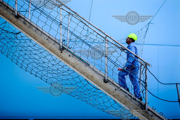 A crew member walks onto the Mary Maersk, the largest container ship in the world.