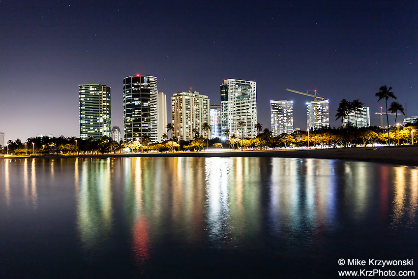 View of buildings at night with lights reflecting on water, Ala Moana Beach Park, Honolulu