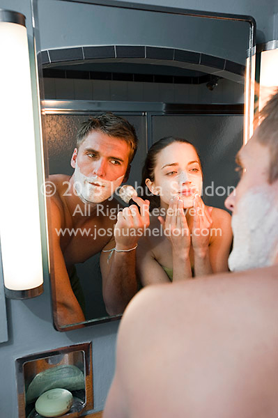 Reflection of young couple shaving and washing face in bathroom mirror