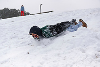 JP Aod (CQ) slides down a hill Monday February 15, 2021, behind the First Presbyterian Early Learning Center in Rogers.  <br /> (NWA Democrat-Gazette/Spencer Tirey)
