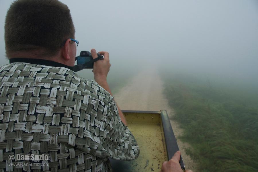 Herpetologist Hinrich Kaiser photographs the foggy landscape from the back of a truck on Atauro Island, Timor-Leste (East Timor)
