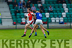 Rathmore's George O'Keeffe jumps clear of the tackle of Laune Rangers David Mangan during their IFC clash in Killarney Friday evening
