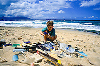 A young boy,age 8,examines a variety of plastic garbage that washed up on Oahu's beautiful beaches.