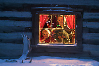 Leo and Julia Hicker peer out of the window of their historic log cabin in winter, Wiseman, Alaska.