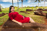 A young pregnant Asian woman rests on a large birthstone with a wish to receive a blessing at the sacred and historical Kukaniloko Birthstones State Monument, Wahiawa, O'ahu.