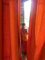 A Buddhist Monk looking out the window from his quarters, at a Monastery in Battambang. Cambodia