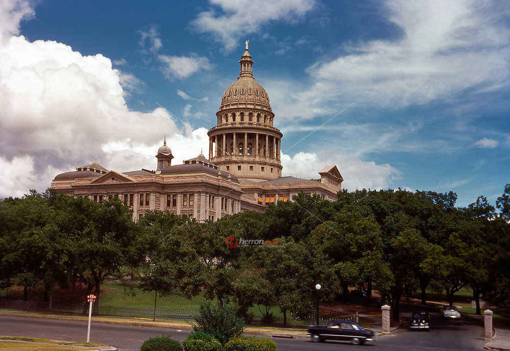 In this 1950 image of Texas State Capitol Building vintage cars line the capital complex in Austin on a beautiful summer's day.