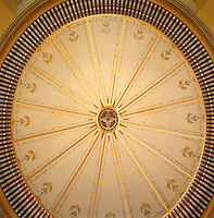 A view of the oval, domed ceiling from directly bellow, with several lights glinting like stars in a painted firmament