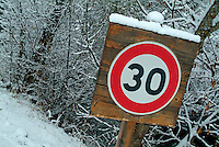 Snow-covered road warning sign informing drivers of the speed limit, Selonnet, French Alps, France.