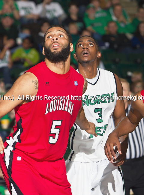Louisiana Lafayette Ragin Cajuns forward J.J. Thomas (5) and North Texas Mean Green guard Alzee Williams (3) in action during the game between the Louisiana Lafayette Ragin Cajuns and the University of North Texas Mean Green at the North Texas Coliseum,the Super Pit, in Denton, Texas. Louisiana Lafayette defeats UNT 57 to 53.