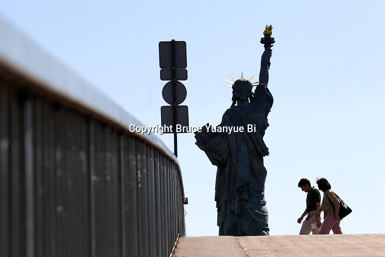 A couple walking by the Replicas of the Statue of Liberty on Île des Cygnes(Isle of the Swans) in River Seine. Paris. France