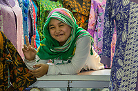 Yogyakarta, Java, Indonesia.  Young Woman Clerk in a Clothing Shop, Beringharjo Market.  Making the V sign is a common gesture in Indonesia when the person being photographed wants the photo to be a good one.