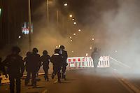 """Nach den pogromartigen Ausschreitungen gegen eine Fluechtlinsunterkunft im saechschen Heidenau am Freitag den 21. August 2015 durch Anwohnerinnen der Ortschaft, kamen am Samstag de 22. August 2015 ca. 250 Menschen in die Ortschaft um ihre Solidaritaet mit den Gefluechteten zu zeigen.<br /> Am Vorabend hatten Rassisten, Nazis und Hooligans sich zum Teil Strassenschlachten mit der Polizei geliefert um zu verhindern, dass Fluechtlinge in einen umgebauten Baumarkt einziehen. Ueber 30 Polizisten wurden dabei verletzt.<br /> Bis in die Abendstunden des 22. August blieb es trotz spuerbarer Anspannung um die Unterkunft ruhig. Im Laufe des Tages wurden immer wieder Gefluechtete mit Reisebussen gebracht was von den wartenenden Heidenauern mit Buh-Rufen begleitet wurde. Vereinzelt wurde auch """"Sieg Heil"""" gerufen, was die Polizei jedoch nicht verfolgte.<br /> Kurz vor 23 Uhr griffen Nazis und Hooligans wie am Vorabend die Polizei mit Steinen, Flaschen, Feuerwerkskoerpern und Baustellenmaterial an. Die Polizei mussten mehrfach den Rueckzug antreten, scheuchte den Mob dann von der Fluechtlingsunterkunft weg. Dabei wurden auch wieder Traenengasgranaten verschossen. Mindestens ein Nazi wurde festgenommen.<br /> Im Bild: Die Polizei hat die Angreifer einige hundert Meter verscheucht und wartet ab.<br /> 22.8.2015, Heidenau/Sachsen<br /> Copyright: Christian-Ditsch.de<br /> [Inhaltsveraendernde Manipulation des Fotos nur nach ausdruecklicher Genehmigung des Fotografen. Vereinbarungen ueber Abtretung von Persoenlichkeitsrechten/Model Release der abgebildeten Person/Personen liegen nicht vor. NO MODEL RELEASE! Nur fuer Redaktionelle Zwecke. Don't publish without copyright Christian-Ditsch.de, Veroeffentlichung nur mit Fotografennennung, sowie gegen Honorar, MwSt. und Beleg. Konto: I N G - D i B a, IBAN DE58500105175400192269, BIC INGDDEFFXXX, Kontakt: post@christian-ditsch.de<br /> Bei der Bearbeitung der Dateiinformationen darf die Urheberkennzeichnung in den EXIF- und  IPTC-Daten nich"""