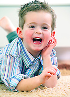 Young toddler boy playing and laughing indoors.