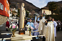 "Switzerland. Canton Ticino. Pregassona. Religious procession. Don Darius Solo is a catholic priest from the Democratic Republic of the Congo. He is blessing with a thurible a wooden sculpture of The Virgin Mary holding the baby Jesus during the ""Festa patronale La Candelora"". Mary was a 1st-century BC Galilean Jewish woman of Nazareth, and the mother of Jesus, according to the New Testament. Christians believe that she conceived her son while a virgin by the Holy Spirit. The Gospel of Luke begins its account of Mary's life with the Annunciation, when the angel Gabriel appeared to Mary and announced her divine selection to be the mother of Jesus. The Catholic Church holds distinctive Marian dogmas, namely her status as the Mother of God, her Immaculate Conception, her perpetual virginity, and her Assumption into heaven. Pregassona is quarter of the city of Lugano and a former municipality in the district of Lugano. A thurible (via Old French from Medieval Latin turibulum) is a metal censer suspended from chains, in which incense is burned during worship services. The Democratic Republic of the Congo (République démocratique du Congo), also known as DR Congo, DRC, the former Belgian Congo, East Congo, Congo-Kinshasa or simply the Congo, is a country located in Central Africa. 4.02.2018 © 2018 Didier Ruef"