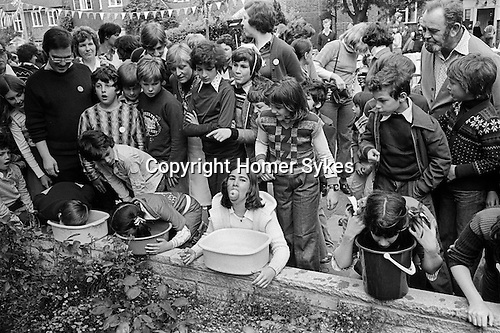 Silver Jubilee Street Party 1977 Hampstead Garden suburb. Children playing in a Apple Dunking or Apple Bobbing or Bobbing for Apples  competition.<br /> <br /> My ref 9/2065/,1977,