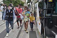 CALI - COLOMBIA, 14-04-2020: Familias enteras suben a los buses durante la jornada de repatriación de 215 venezolanos hacía su país desde Cali en el día 22 de la cuarentena total en el territorio colombiano causada por la pandemia  del Coronavirus, COVID-19. / Whole families get on the buses during the repatriation journey of 215 Venezuelans to their country from Cali during the day 22 of total quarantine in Colombian territory caused by the Coronavirus pandemic, COVID-19. Photo: VizzorImage / Gabriel Aponte / Staff