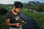 Fishing Cat (Prionailurus viverrinus) biologist, Anya Ratnayaka, setting up camera trap in urban wetland, Urban Fishing Cat Project, Diyasaru Park, Colombo, Sri Lanka