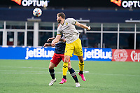 FOXBOROUGH, MA - MAY 16: Josh Williams #3 Columbus SC heads the ball away from Gustavo Bou #7 of New England Revolution during a game between Columbus SC and New England Revolution at Gillette Stadium on May 16, 2021 in Foxborough, Massachusetts.