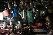 Fishmongers sell juvenile yellow tuna fish in the old market in Puerto Princesa in the Philippines.<br /> Photograph: Sanjit Das/Panos for Greenpeace