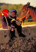 Two little girls visiting a horse. Amish girls. Strasburg Pennsylvania USA Lancaster County.