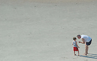 A father gives counsel to his son about throwing sand at his sister at Virginia Beach, Va.