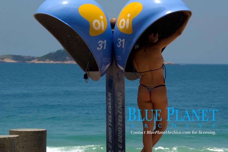 Woman in bikini calling from a public telephone at Ipanema beach, Rio de Janeiro, Brazil