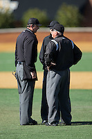 Umpires Drew Maher (left), Gerald Trexler (right) and Thomas Newsom discuss a call during the NCAA baseball game between the Richmond Spiders and the Wake Forest Demon Deacons at David F. Couch Ballpark on March 6, 2016 in Winston-Salem, North Carolina.  The Demon Deacons defeated the Spiders 17-4.  (Brian Westerholt/Four Seam Images)