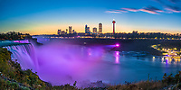 Amazing Niagara Falls panorama with water lit up in purple under a clear blue and orange sky, USA and Canada