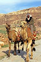 Bedouin riding a camel near the Royal Tombs, Petra, Jordan.