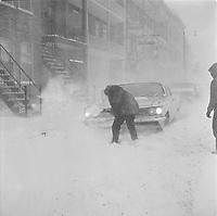 Enfants et adultes pelletent la neige pour degager une voiture,durant une tempete de neige, novembre 1965 (date exacte inconnue, possiblement vers le 18) dans la ville Quebec.<br /> <br /> PHOTO : Agence Quebec Presse